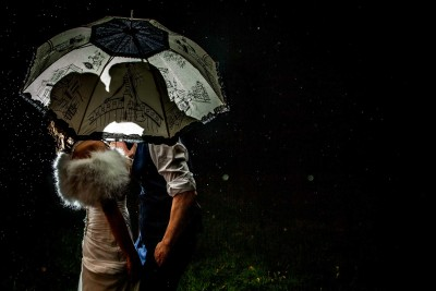 bride and groom under an umbrella catching the raindrops