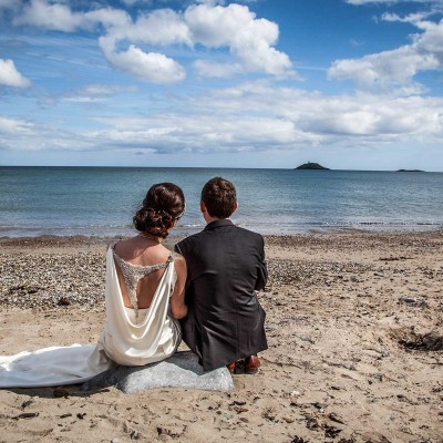 bride and groom sitting on the beach at garryvoe, cork