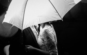 Bride and groom under an umbrella in the rain.