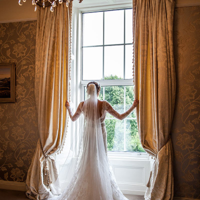 Bride at window opening curtains