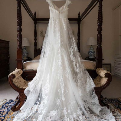 Bride's wedding dress hanging on four poster bed