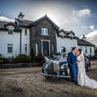 Bride and groom with bridal car