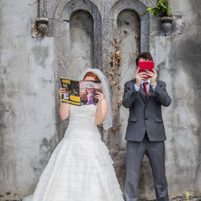 Bride and groom covered by comic book and game boy.