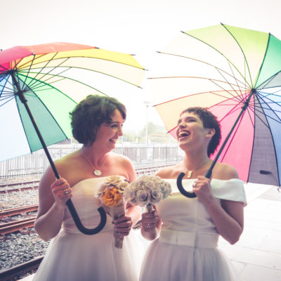 Two brides with Rainbow umbrellas