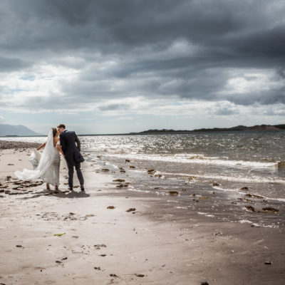 newly weds kissing on beach during photoshoot