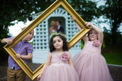 cute kids helping by framing newlyweds