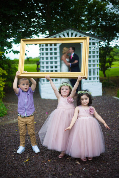 Kids framing kissing newlyweds